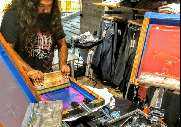 Screen printing a t-shirt live at an event activation.